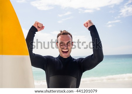 Portrait of happy man with surfboard standing on the beach - stock photo