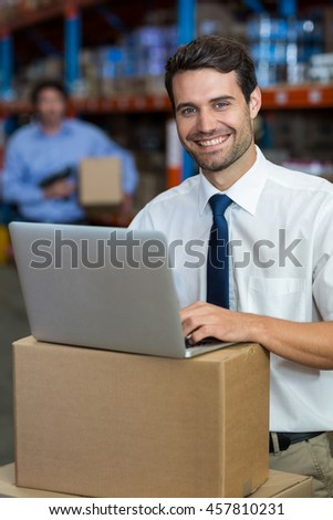 Portrait of happy manager using a laptop put on cardboard in a warehouse