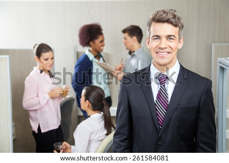 Portrait of happy manager with employees discussing in background at call center in call center