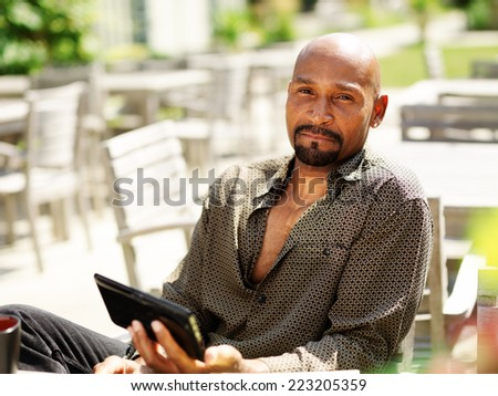 portrait of happy mature african man with smart phone - stock photo