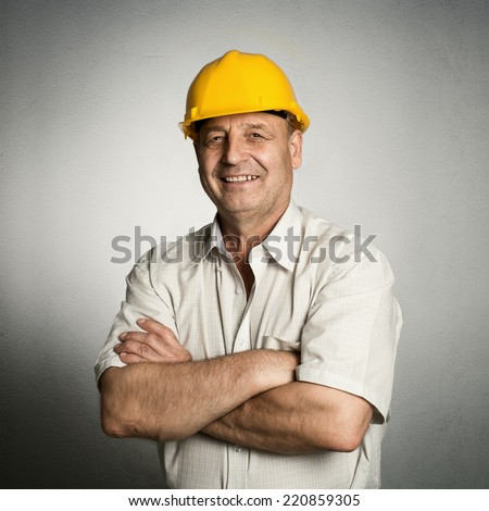 Portrait of happy mature architect in helmet standing with crossed arms. Male industrial inspector of 50s wearing uniform posing in studio.  - stock photo