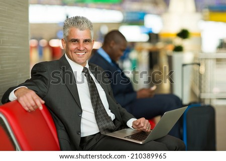 portrait of happy mature business traveler using laptop at airport - stock photo