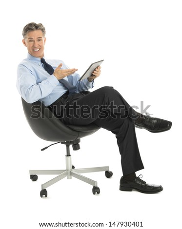 Portrait of happy mature businessman gesturing at digital tablet while sitting on office chair against white background - stock photo