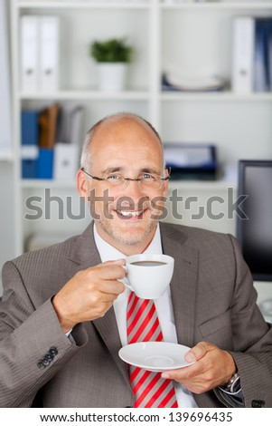 Portrait of happy mature businessman having coffee in office - stock photo