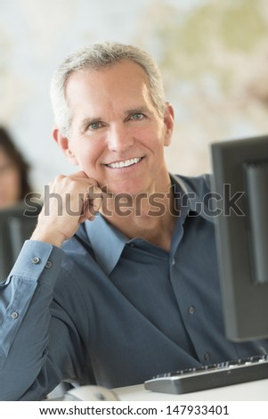 Portrait of happy mature businessman leaning at computer desk in office - stock photo