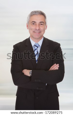 Portrait Of Happy Mature Businessman With Arm Crossed - stock photo