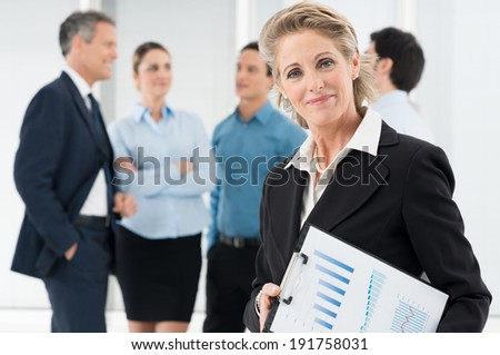 Portrait Of Happy Mature Businesswoman Holding Clipboard - stock photo