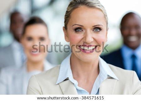 portrait of happy mature businesswoman in front of colleagues - stock photo