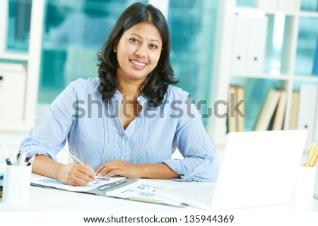 Portrait of happy mature businesswoman looking at camera while working in office - stock photo