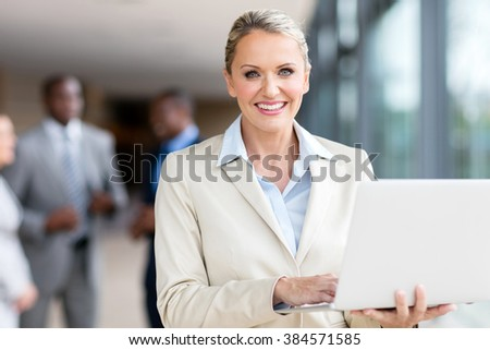 portrait of happy mature businesswoman using laptop computer - stock photo