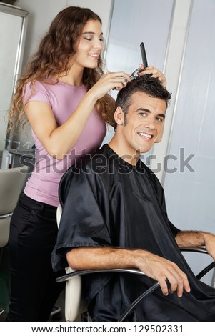 Portrait of happy mature client getting haircut in salon - stock photo