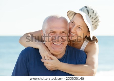 Portrait of Happy mature couple against sea and sky - stock photo