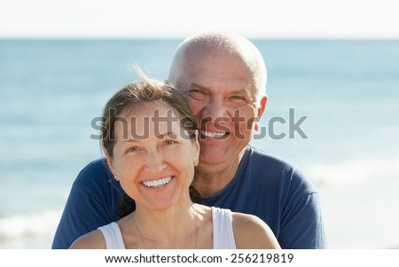 Portrait of Happy mature couple against sea and sky background - stock photo