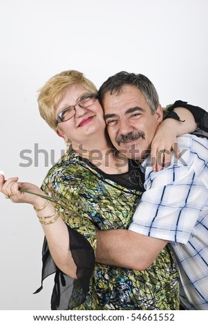 Portrait of happy mature couple 502 embracing in front of image and smiling - stock photo