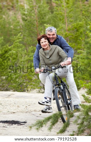 Portrait of happy mature couple riding bicycle - stock photo
