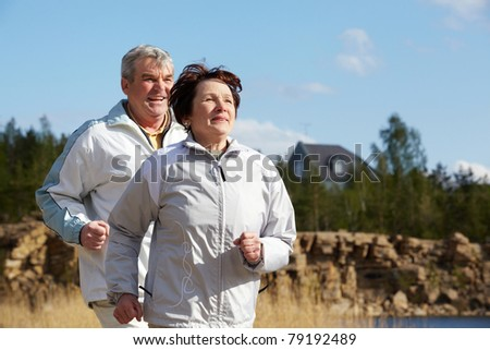 Portrait of happy mature couple running together - stock photo