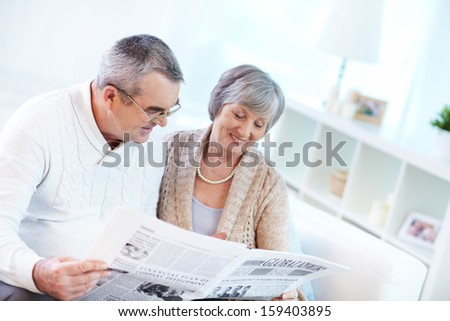 Portrait of happy mature couple sitting at home and reading newspaper together - stock photo