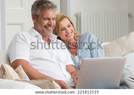 Portrait Of Happy Mature Couple Sitting On Couch Using Laptop - stock photo