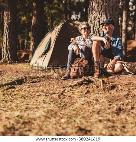 Portrait of happy mature couple sitting together under a tree in forest. Senior man and woman relaxing at their campsite. - stock photo