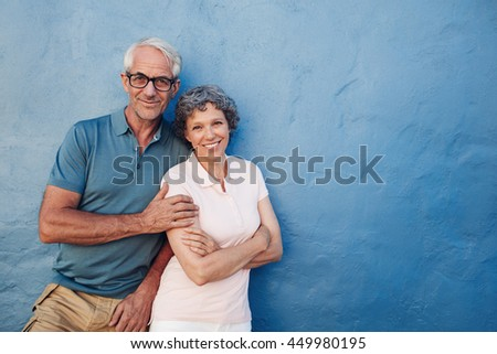 Portrait of happy mature couple standing together against blue wall. Middle aged man and woman looking at camera and smiling on blue background - stock photo