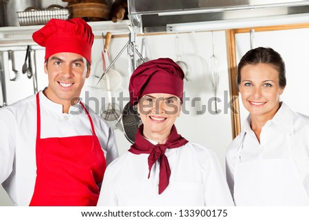 Portrait of happy mature female chef with colleagues in commercial kitchen - stock photo
