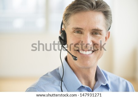Portrait of happy mature male customer service representative wearing headset - stock photo