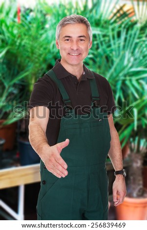 Portrait Of Happy Mature Male Gardener Extending His Hand To Shake - stock photo