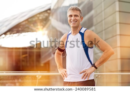 Portrait Of Happy Mature Male Jogger With Earphone Looking At Camera Outdoor - stock photo