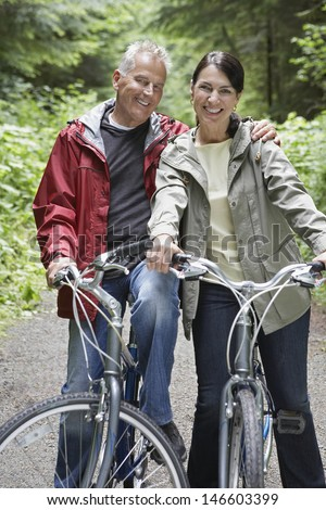 Portrait of happy mature man and middle aged woman with bikes in forest - stock photo