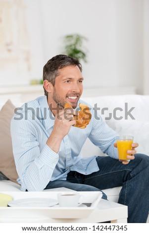 Portrait of happy mature man having breakfast on sofa - stock photo