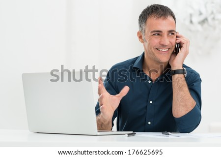 Portrait Of Happy Mature Man In Front Of Laptop Talking On Cellphone - stock photo