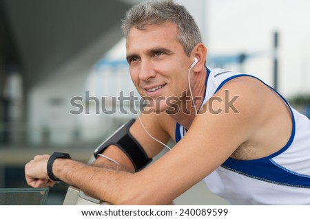 Portrait Of Happy Mature Man Listening Music On Earphones - stock photo