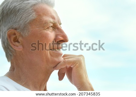 Portrait of happy mature man over blue sky