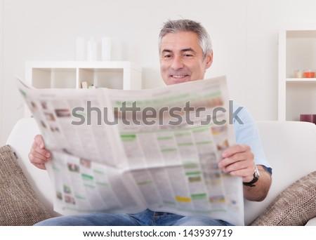 Portrait Of Happy Mature Man Reading Newspaper - stock photo