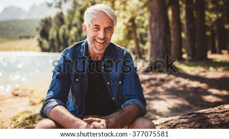 Portrait of happy mature man sitting near a lake looking at camera and smiling. Senior caucasian man sitting on a log by the lake on a summer day. - stock photo
