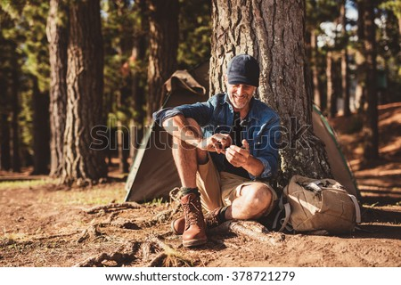 Portrait of happy mature man sitting under a tree with mobile phone. Senior man sitting at campsite in forest. - stock photo