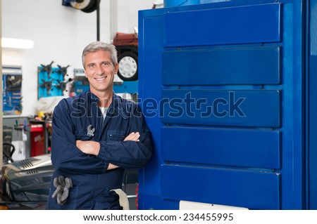 Portrait Of Happy Mature Mechanic At Repair Service Station, Blue Banners for your text - stock photo