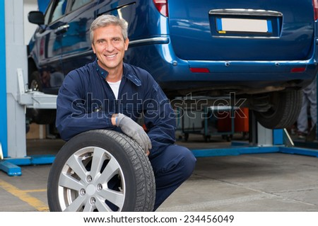 Portrait Of Happy Mature Mechanic At Repair Service Station Holding A Tyre - stock photo