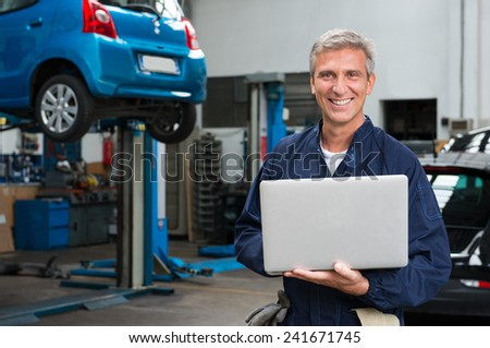 Portrait Of Happy Mature Mechanic At Repair Service Station With Laptop - stock photo