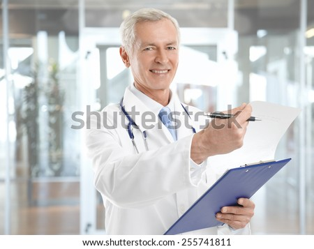 Portrait of happy mature medical doctor standing at clinic.  - stock photo