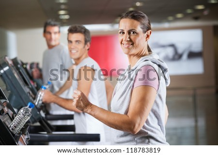 Portrait of happy mature woman and men running on treadmill in fitness center