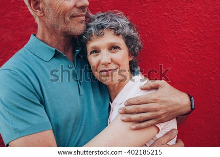 Portrait of happy mature woman embracing her husband against red background. Affectionate couple together against red background. - stock photo