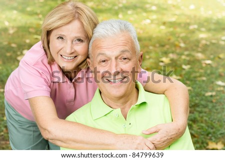 Portrait of happy mature woman hugging her husband in the park. - stock photo