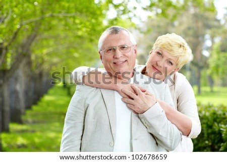 Portrait of happy mature woman hugging her husband outside - stock photo