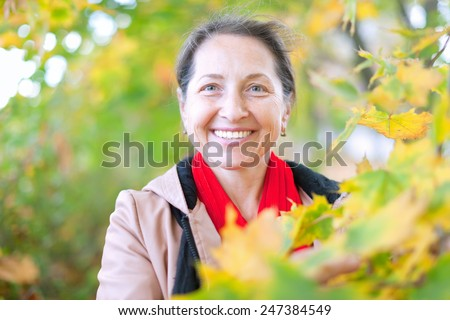Portrait of happy mature woman  in autumn park - stock photo