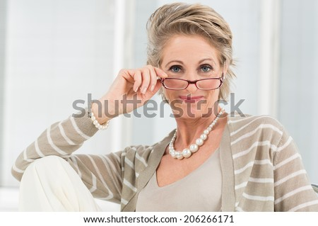 Portrait Of Happy Mature Woman Looking Through Glasses - stock photo