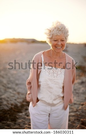 Portrait of happy mature woman walking on the beach. Beautiful old caucasian lady walking with smile on face - Outdoors - stock photo