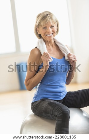 Portrait of happy mature woman with towel around neck sitting on fitness ball at home - stock photo