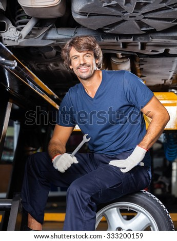 Portrait of happy mechanic holding wrench while sitting under lifted car at auto repair shop