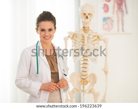 Portrait of happy medical doctor woman teaching anatomy using human skeleton model - stock photo